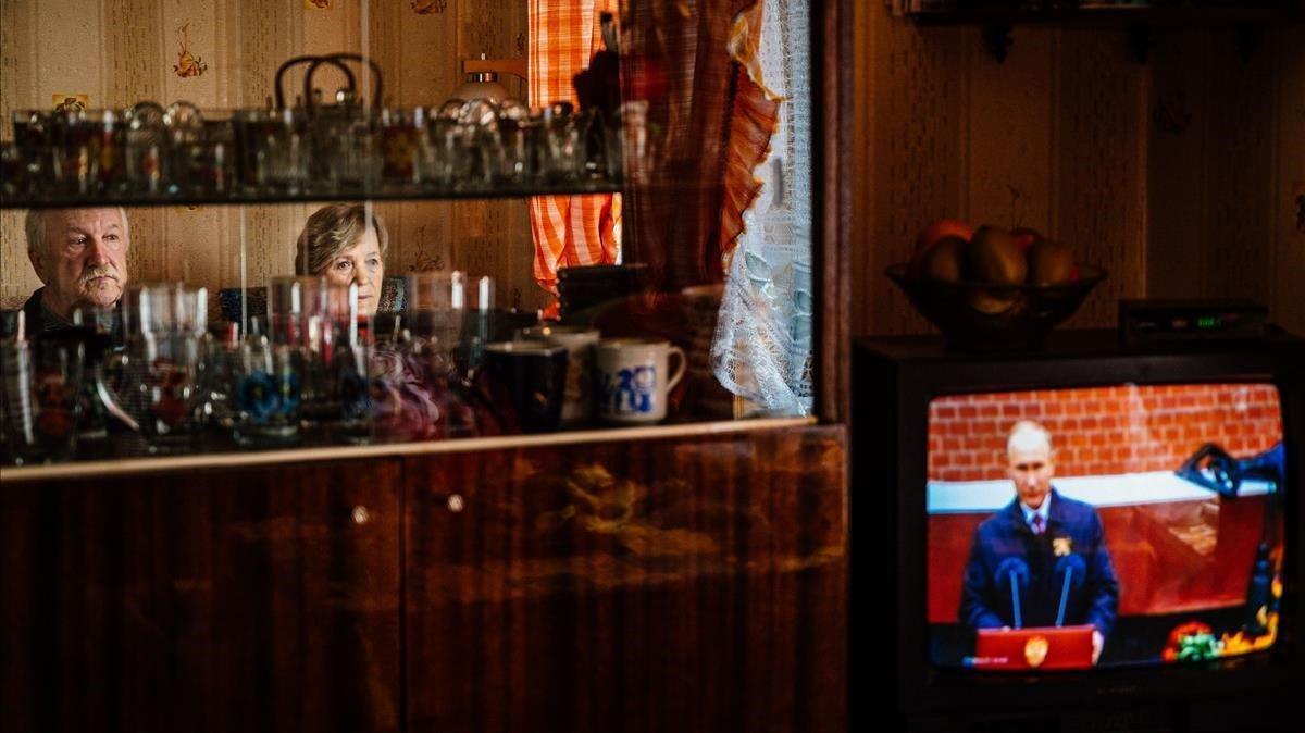 Gennady Matveiev y su esposa Galina miran la pantalla de televisión durante un discurso del presidente ruso Vladimir Putin