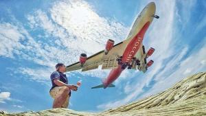 Un turista se fotografía junto a un avión en la playa de Mai Khao (al sur de Tailandia).