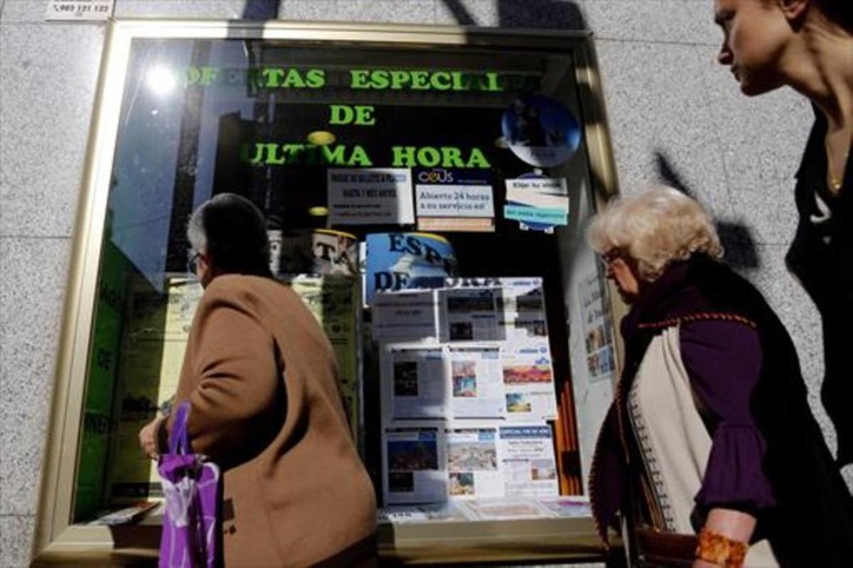 Ofertes 8 Diferents dones miren l'aparador d'una agència de viatges, a Madrid.