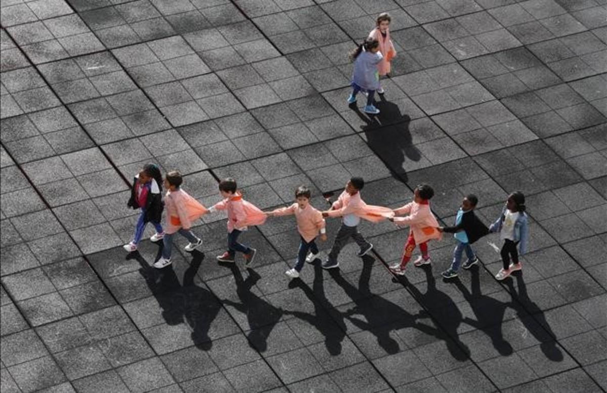 Alumnos de un colegio juegan en el patiomientras hacen una fila.