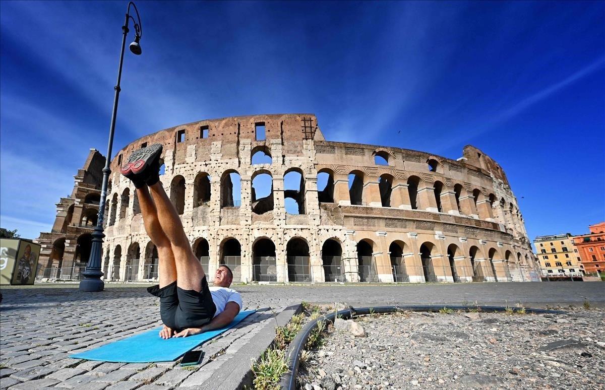 Un hombre se entrenajunto al monumento del Coliseo.