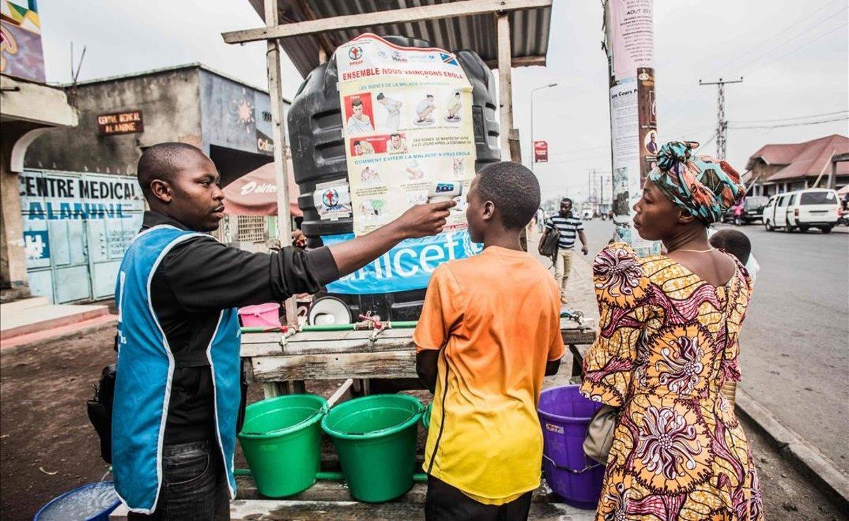 Un trabajador de Unicef mide la temperatura de un niño.