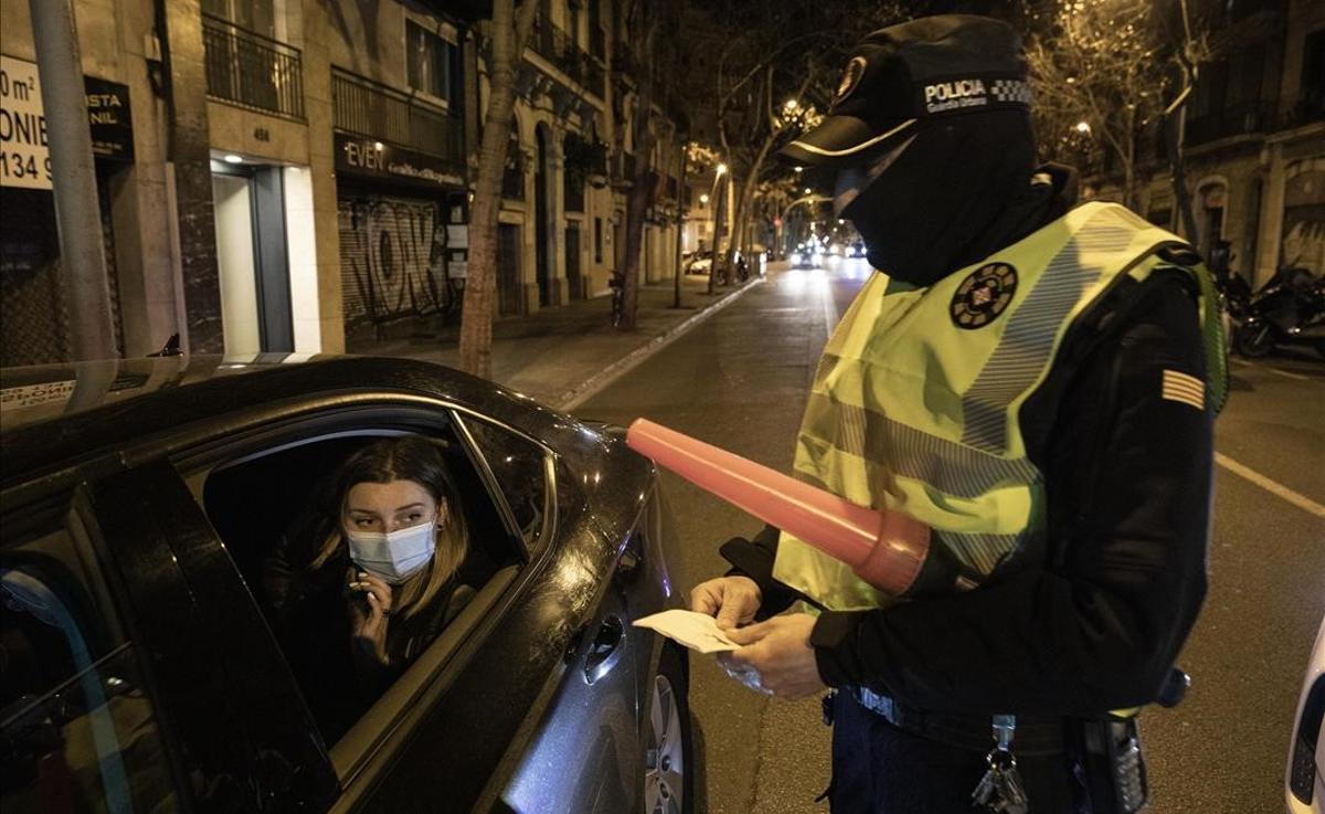 Un agente de la Guàrdia Urbana identifica a unas personas que circulaban por Barcelona fuera del horario permitido sin justificación.