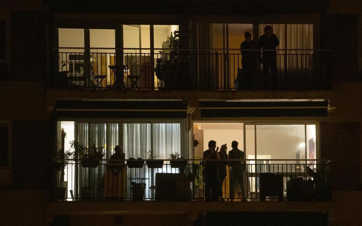 Vecinos confinados en sus pisos, en un bloque de la calle del Escorial, aplauden a los sanitarios.