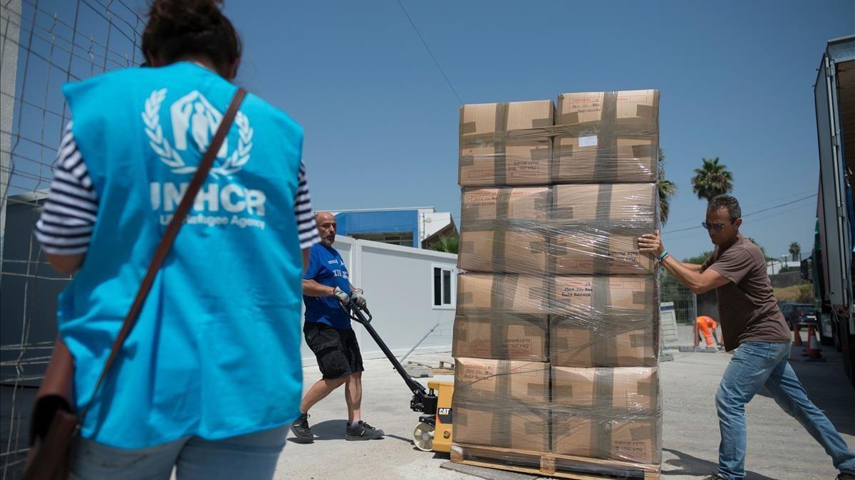 Un grupo de trabajadores descarga suministros en el centro de acogida temporala extranjeros de San Roque, en Cádiz, ayer.