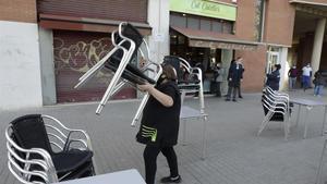 Una mujer recoge las siillas de la terraza de un bar de Poblenou.