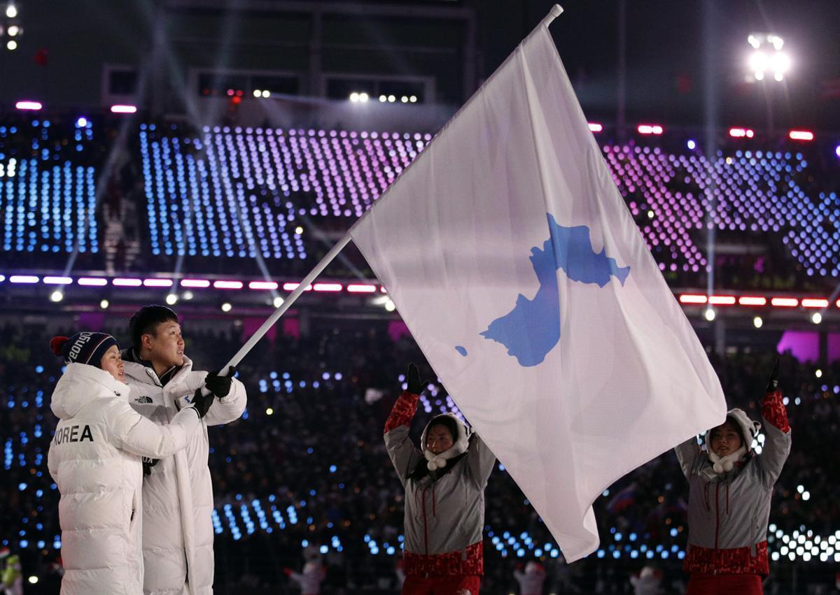 Representantes de Corea del Norte y Corea del Sur desfilan bajo la bandera de la península coreana.