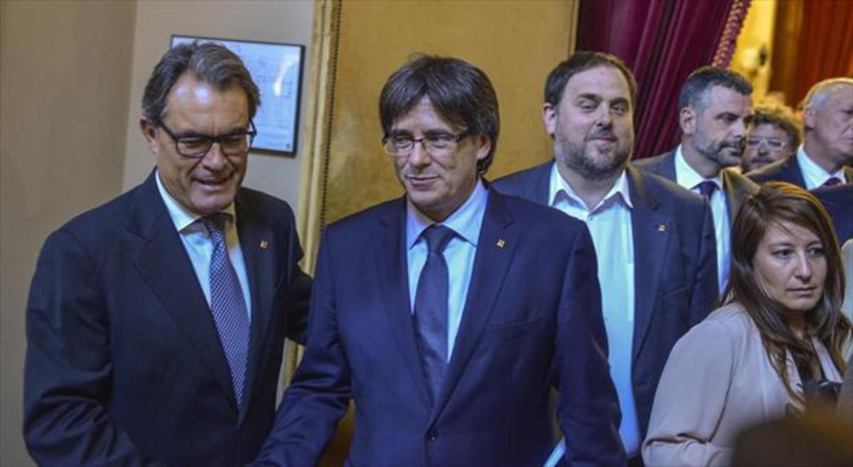 Mas saluda a Puigdemont ante la mirada de Junquerasen el Parlament tras la sesión sobre la moción de confianza.