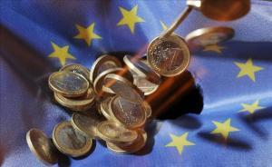 Un puñado de monedas de euro sobre la bandera de la Unión Europea.