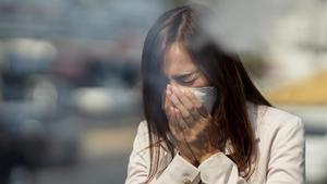 Una mujer tose con una mascarilla puesta.