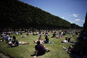 Decenas de parisinos toman el sol en los Jardines de Luxemburgo de París.
