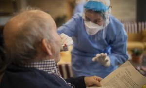 Una voluntaria de Open Arms realiza un test de detección de coronavirus a un ancianoen una residencia de Barcelona.