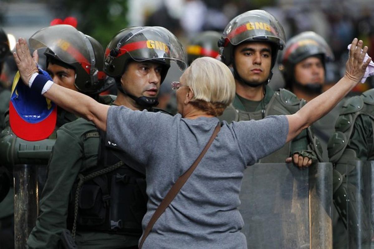 Una manifestante de la oposición se encara con la policía durante una protesta contra el Gobierno de Maduro, el lunes en Caracas.