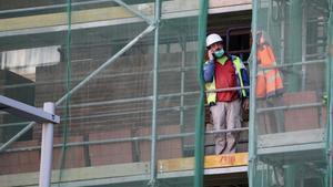Trabajadores de la construcción en un andamio cerca de la Ronda de Dalt de Barceloba, ejerciendo durante la actual pandemia del coronavirus.