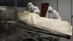 Dos operarios una funeraria preparan el entierro de un fallecido por covid.