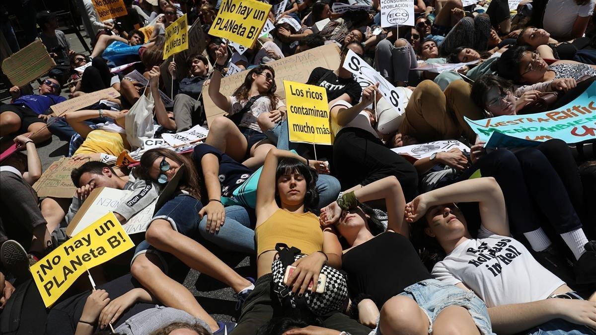 Los manifestantes de Madrid escenifican la situación de emergencia climática echándoseal suelo delante del Congreso
