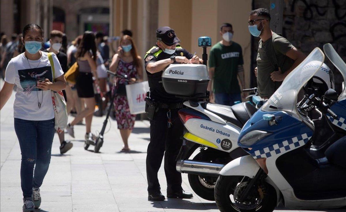 Un policía multa a un ciclista por una infracción y le advierte también de que debe usar mascarilla cuando vaya por la calle, en Barcelona, el pasado 11 de julio.
