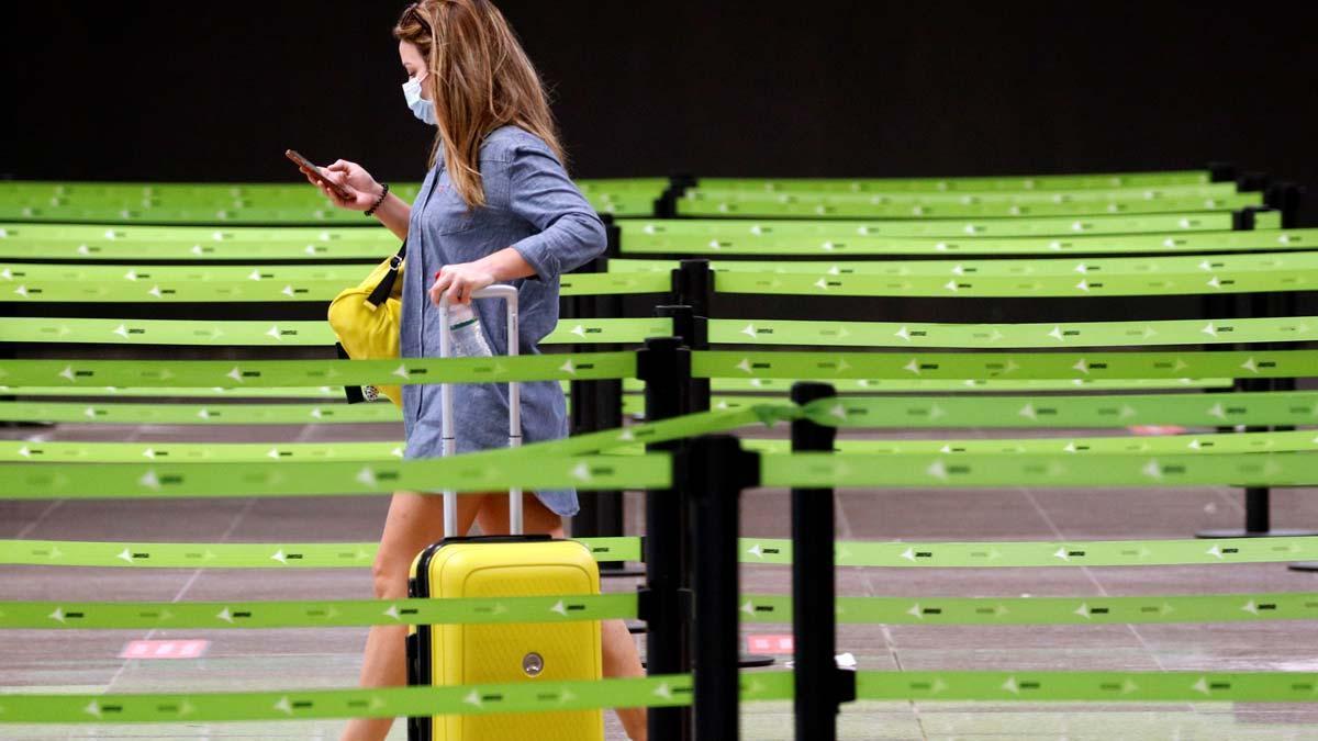 González Laya asegura que España es un país seguro. En la foto, una pasajera se dirige a un mostrador de facturación en el aeropuerto de Barcelona-El Prat.