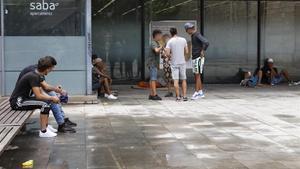 Un educador social (de blanco) habla con unos menores cerca de la parroquia de Santa Anna de Barcelona, el verano pasado.