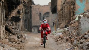 Una mujer iraquí pedalea vestida de Papa Noel entre las ruinas de la ciudad vieja de Mosul