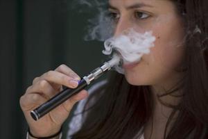 Una mujer exhala vapor de un cigarrillo electrónico.