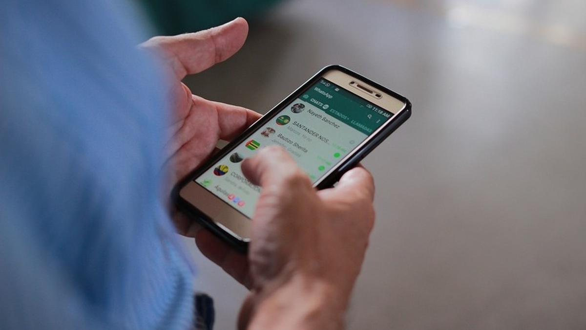 Un hombre usa la aplicación de Whatsapp en su teléfono móvil.