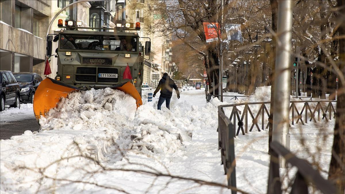 Miembros de la a Unidad Militar de Emergencias (UME) ayudados de una maquina quitanieves trabajan retirando la gran nevada en el Paseo de la Castellana en Madrid
