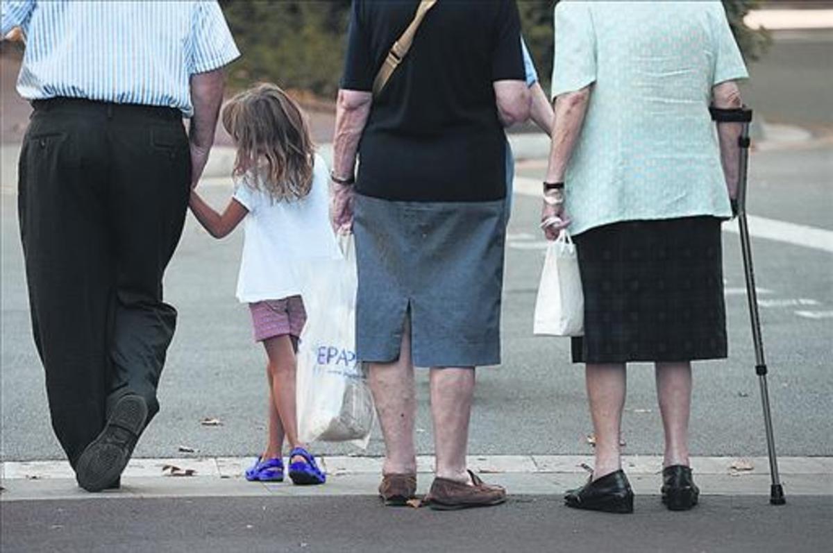 Una niña acompañada de personas mayores, en una calle de Barcelona.