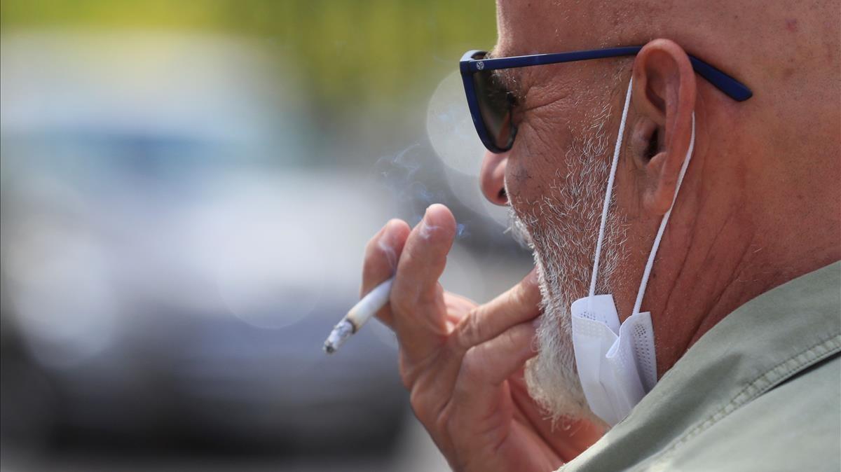 Un hombre fumando en la calle.
