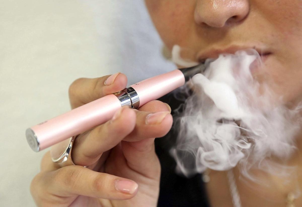 Una mujer fuma un cigarrillo electrónico.