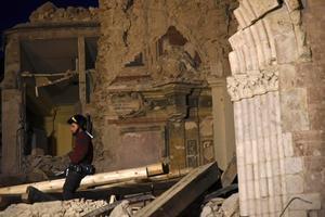 Un bombero trata de recuperar objetos de la basílica de San Benedetto, en Norcia, dañada por los terremotos.