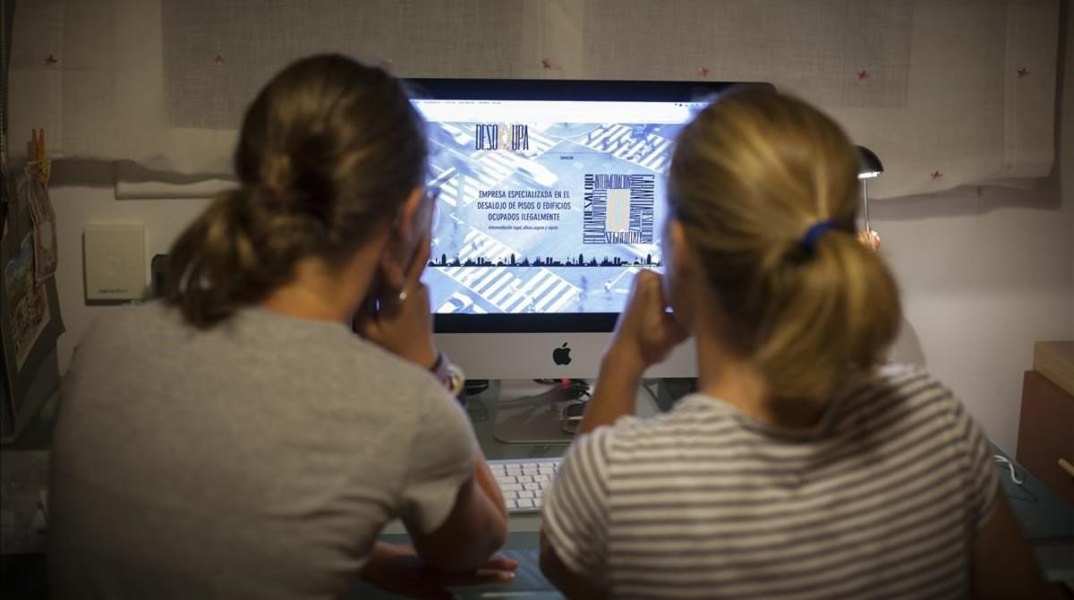 Dos personas consultan la web de Desokupa.
