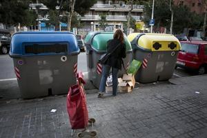 Una mujer deposita residuos en contenedores en Barcelona.
