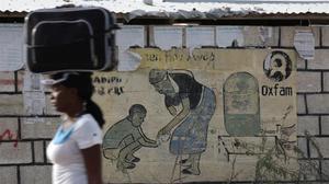 Una mujer pasa por una valla con el logo de Oxfam en el campo de Corail, en Haití.