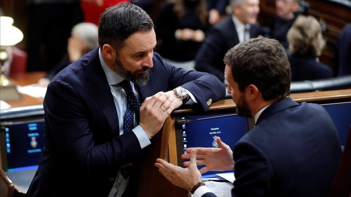 El presidente de Vox, Santiago Abascal, charla con el del PP, Pablo Casado, en el escaño de este en el Congreso.