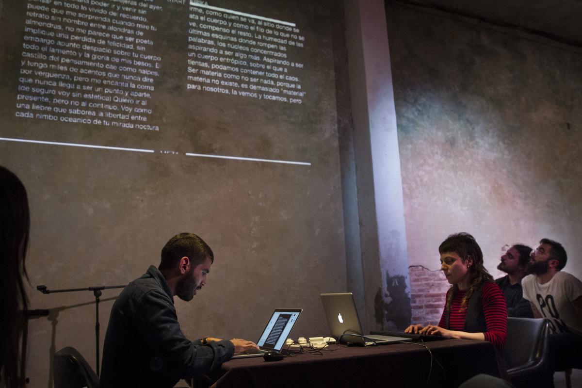 AlexanderMartínezy ErikaRubio improvisan sobre el teclado durante la carrera literaria del VI Slam de Escritura, en el centro de arte Mutuo. Proyectados en la pared, los textos que están escribiendo.