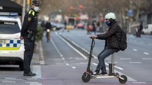 Un usuario del patinete eléctrico circula ante un guardia urbano, en Barcelona