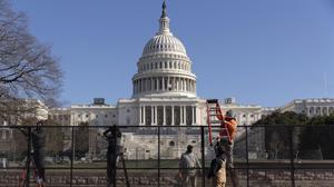Trabajadores levantan una valla metálica alrededor del Capitolio.