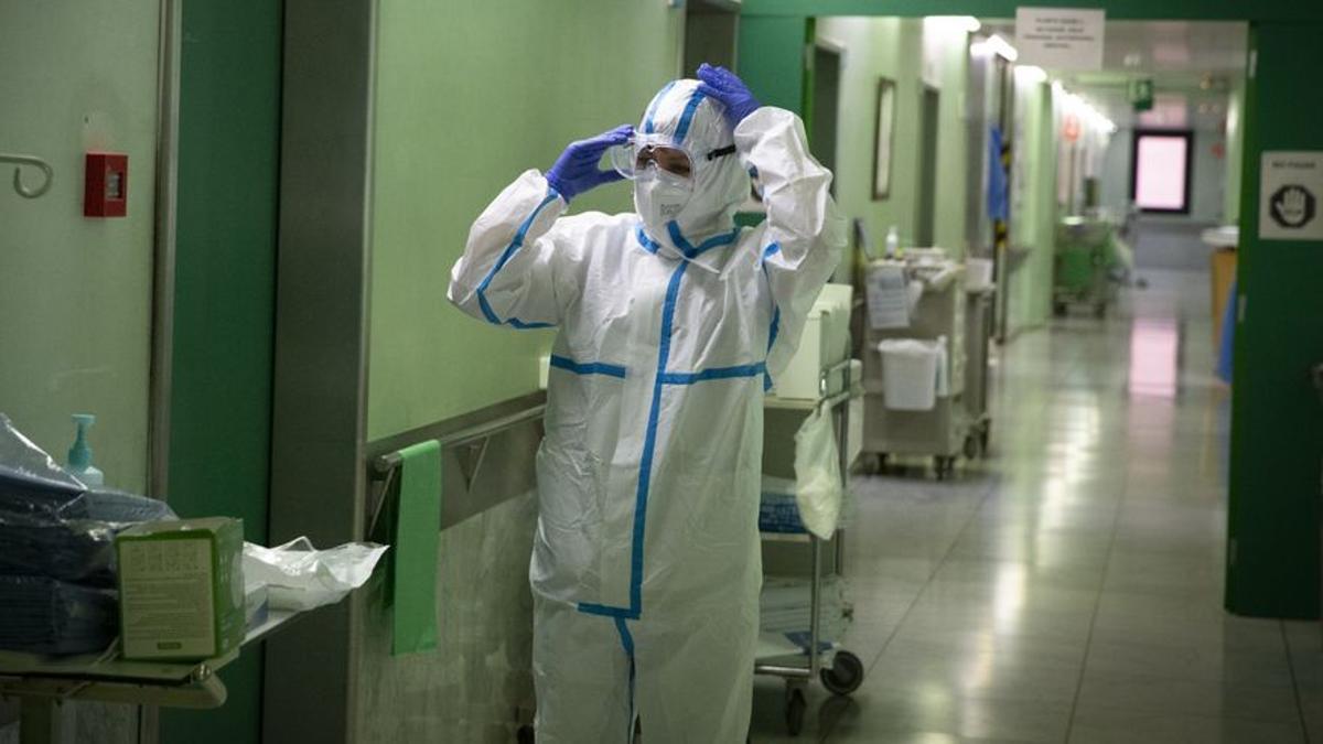 Un sanitario se ajusta las gafas antes de entrar en la habitación de un contagiado