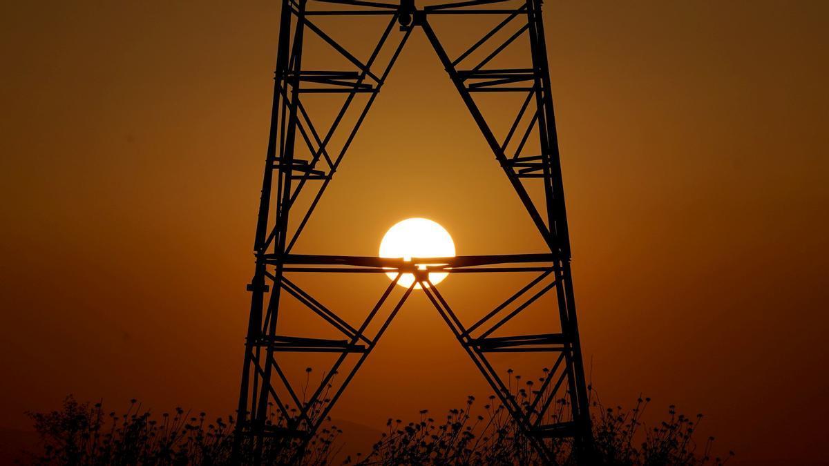 Una torre eléctrica con la puesta de sol