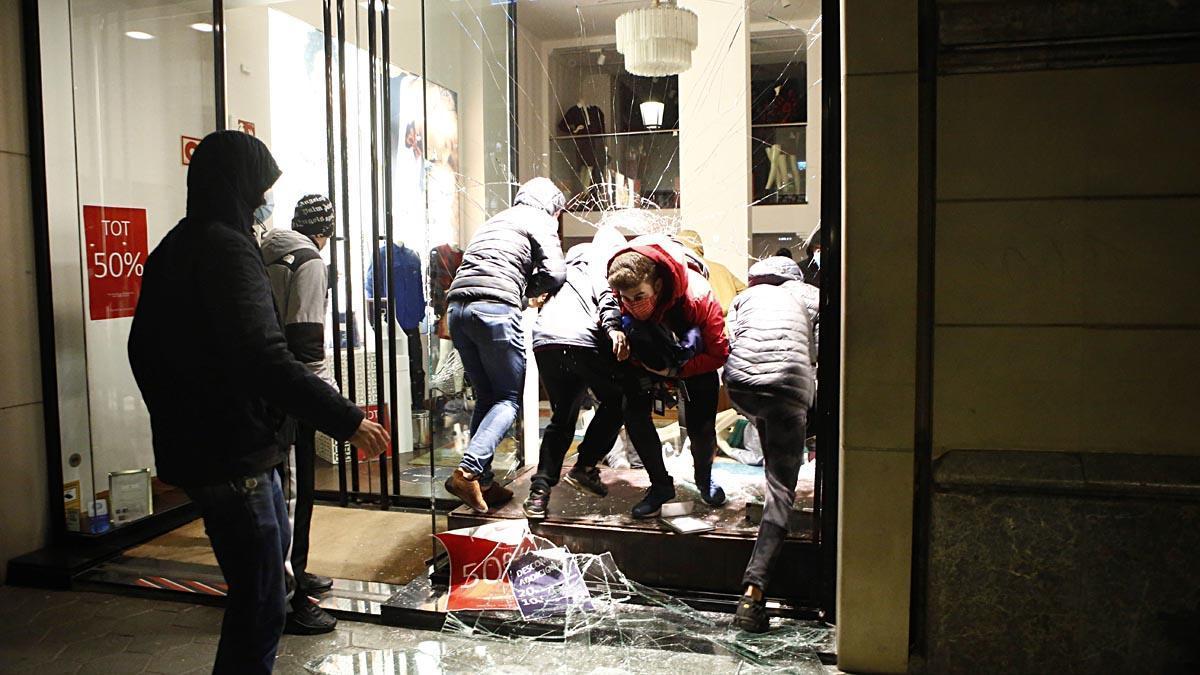 Manifestantes entran en un comercio tras la manifestación celebrada esta tarde en Barcelona.