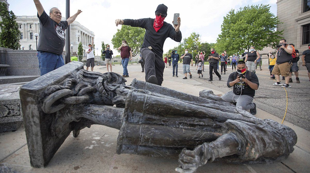 Varios hombres celebran el derribo de una estatua deCristóbal Colón en Saint Paul (Minnesota), el 19 de junio.