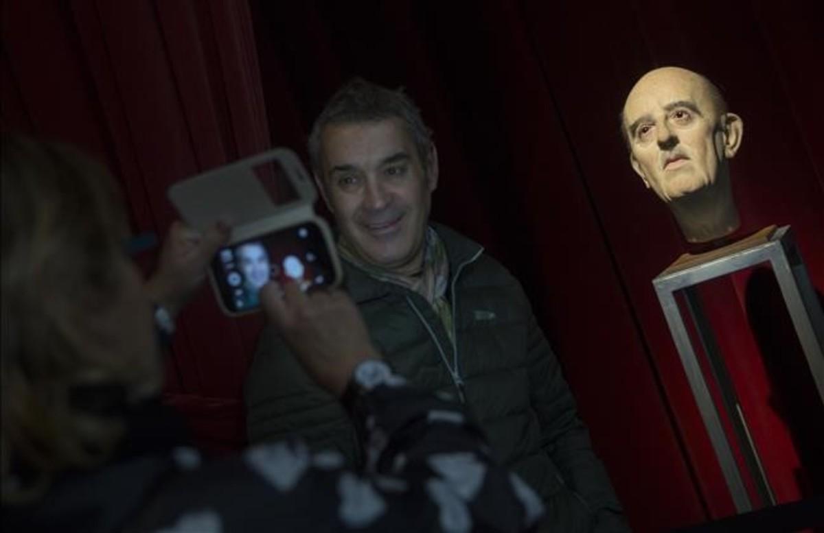 Un visitante se fotografía junto a la inquietante testa cedida por el artista Eugenio Merino.