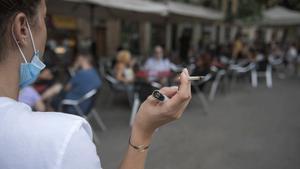 Una mujer fuma alejada de los clientes de una terraza de Barcelona, el pasado 18 de agosto.