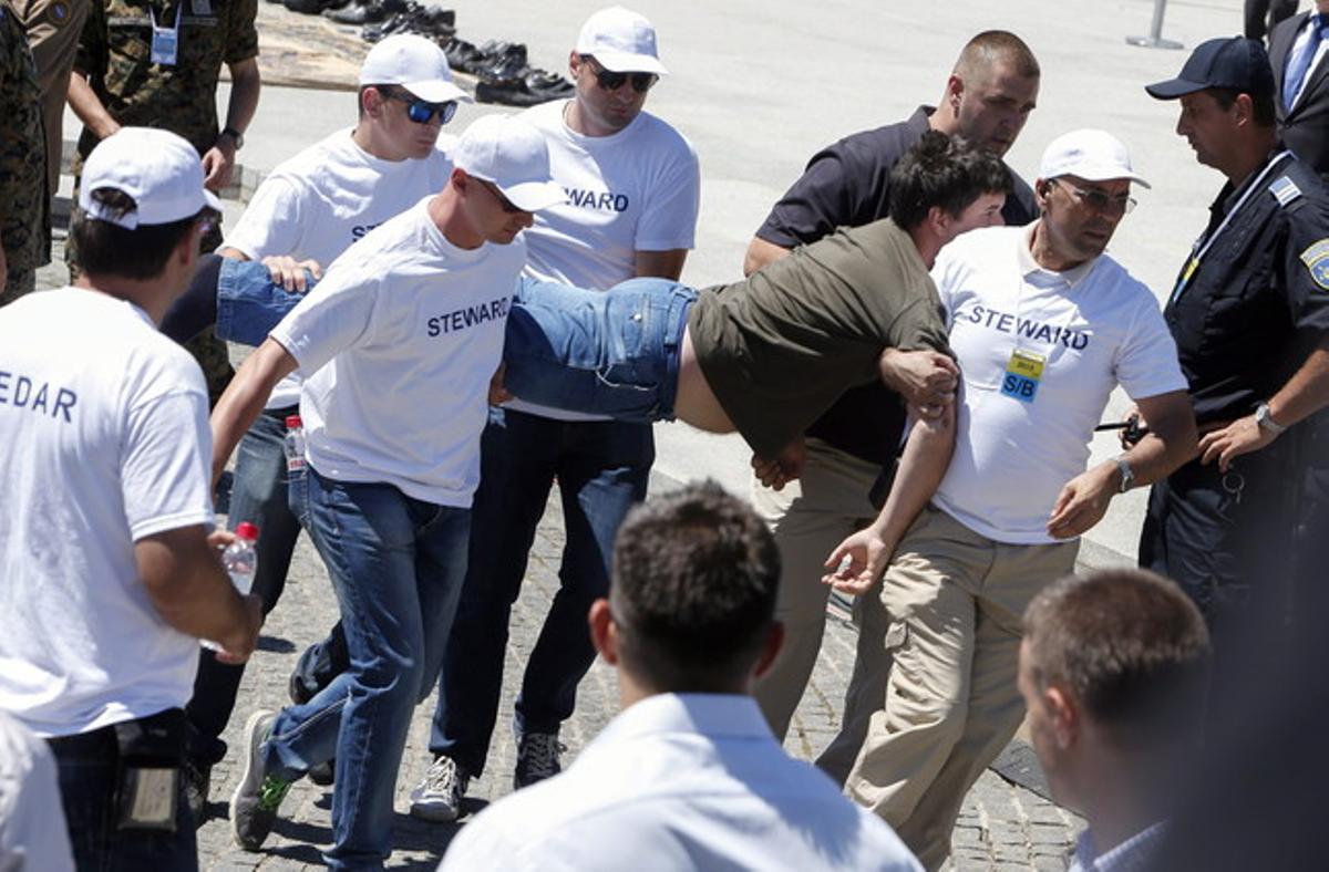 Agentes de seguridad detienen a un hombre tras la agresión a Aleksandar Vucic, primer ministro serbio, en el homenaje a las víctimas de la matanza de Srebrenica.