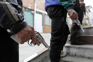 Tres personas sostienen sendas armas en una imagen de archivo tomada en Bogotá.