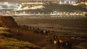 Inmigrantes marroquís caminan por la orilla del mar hacia un acantilado rocoso en la ciudad de Fnideq, en un intento de cruzar desde Marruecos a España desde Ceuta.