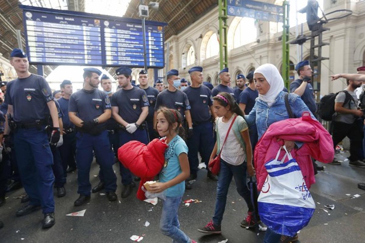 Una familia de refugiados deja la estación más importante del este de Budapest, después de que la policía la cerrara impidiédoles el paso con una valla humana.