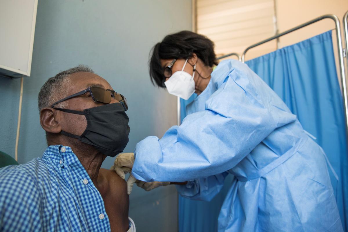 Una enfermera vacuna a un hombre en Haití, el país acaba de recibir el primer lote de dosis anticovid.