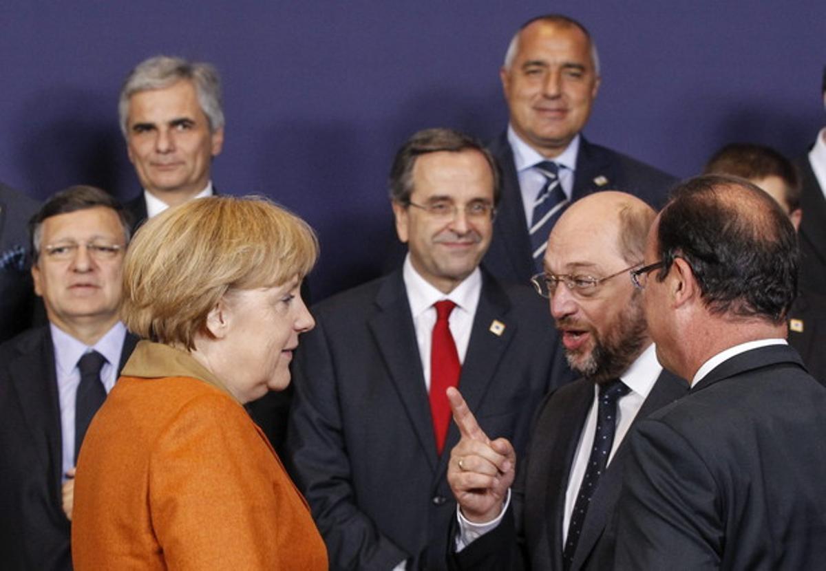 El presidente del Parlamento Europeo, Martin Schulz, se dirige a la cancillera alemana, Angela Merkel, ante el presidente francés, François Hollande (de espaldas), durante la foto de familia, el jueves en Bruselas.